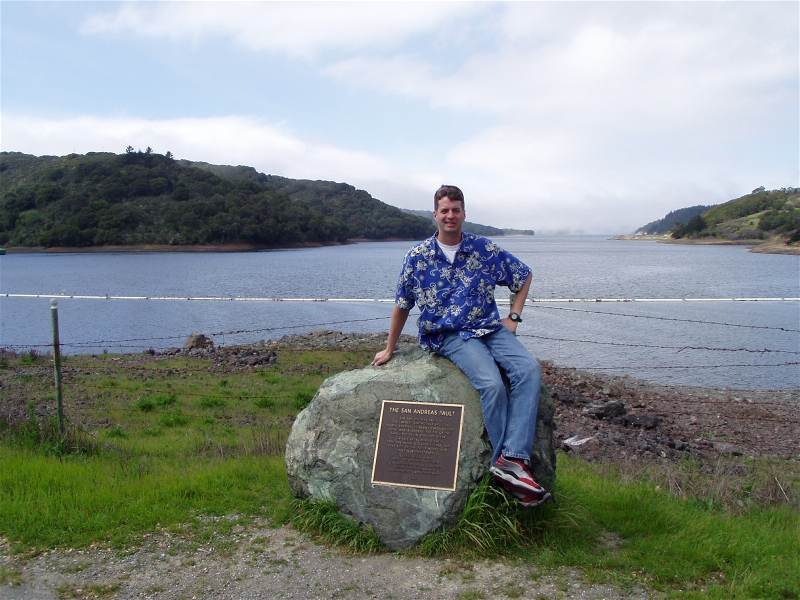 A picture of me sitting on a marker for the San Andreas fault near San Francisco, CA