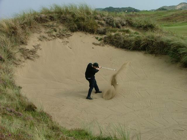 A picture of Tom Sullivan hitting a golf shot out of the 'biggest bunker in Ireland'