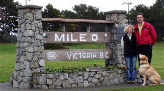 A picture of Martha, Doug and Sam in front of the TransCanada 'Mile 0' sign in Victoria, BC